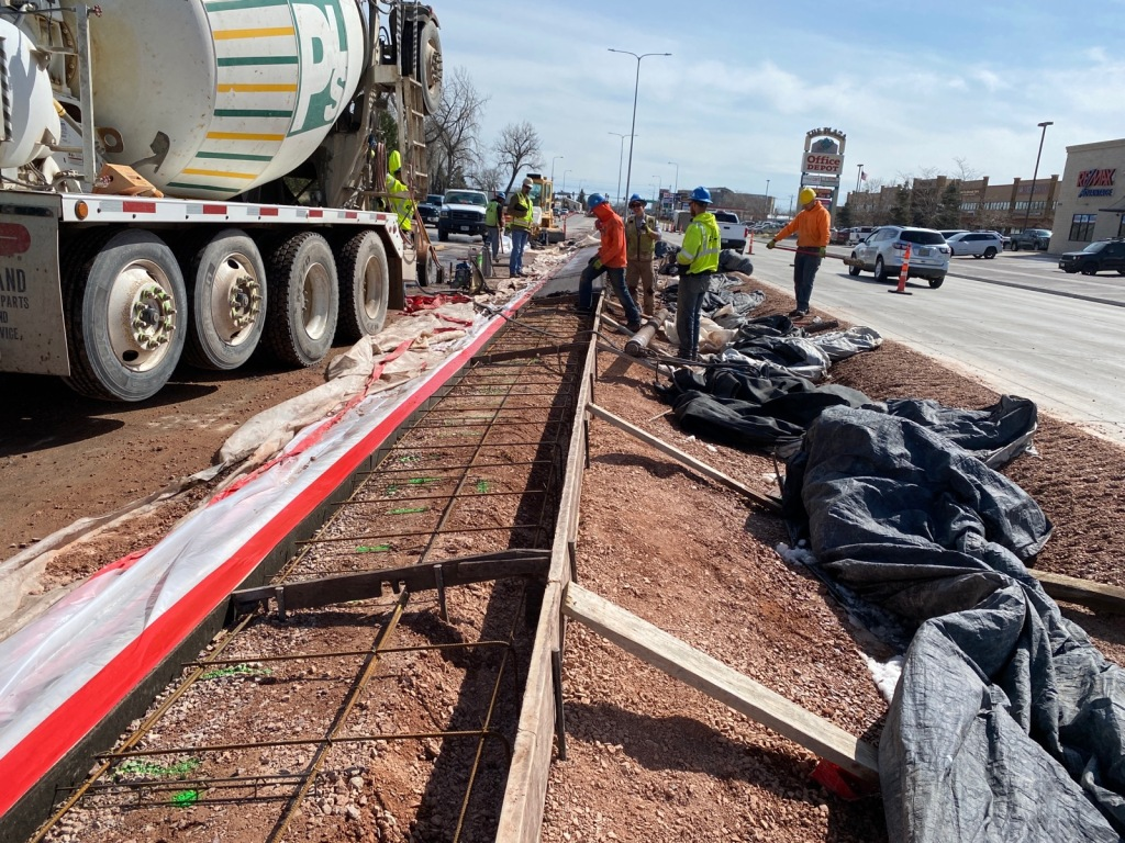 Crews install colored concrete median on Omaha Street in Rapid City, South Dakota, Wednesday, April 7, 2021.